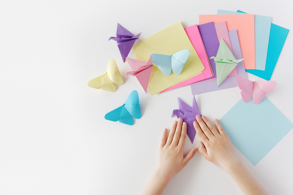 Children's,hands,do,origami,from,colored,paper,on,white,background.